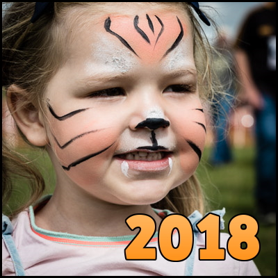 Photo of little girl with face painted as a lion, overlaid with the word '2018'